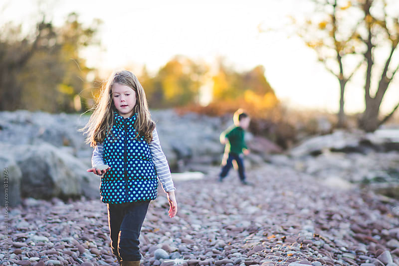 Girl walking away from boy on rock beach by Lindsay Crandall for Stocksy United