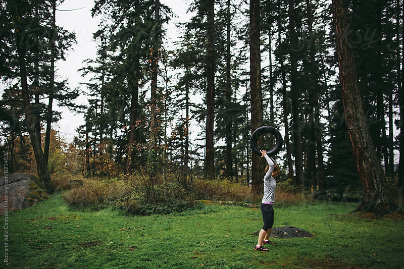 Woman throwing tire near forest at rainy outdoor bootcamp by Rob and Julia Campbell for Stocksy United