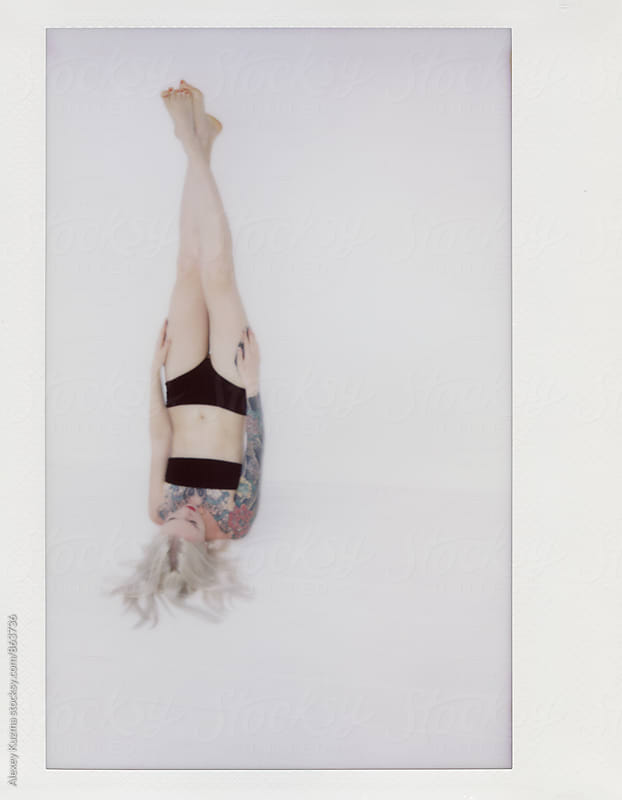 young blond woman upside down on the white background   by Alexey Kuzma for Stocksy United