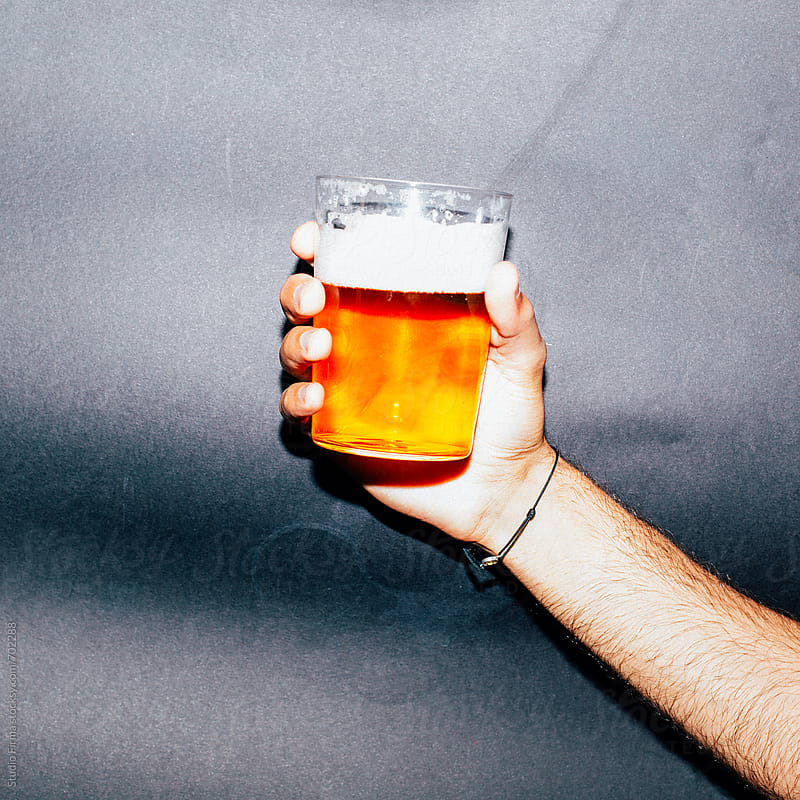 Hand holding Beer. by Studio Firma for Stocksy United
