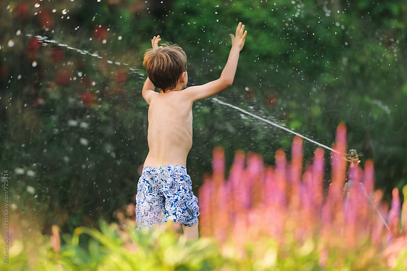 Taken from behind boy running through water sprinkler by Rebecca Spencer for Stocksy United