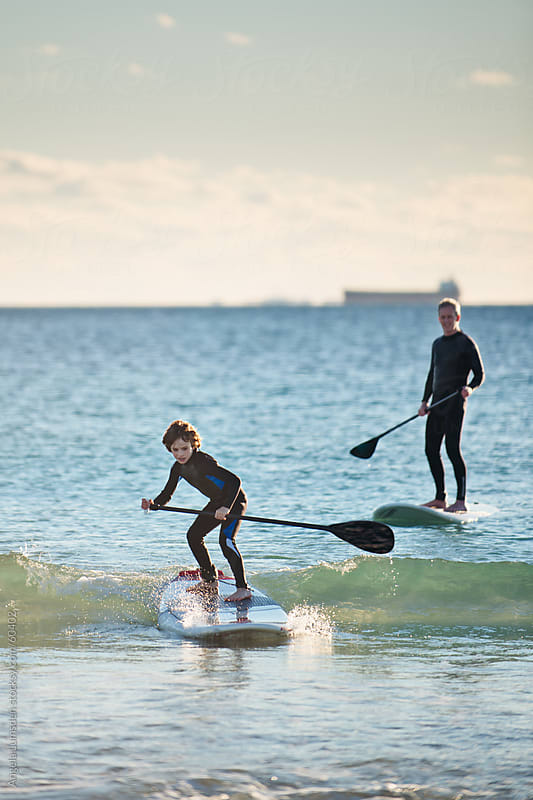 Boy catches a wave on a stand up paddle board while his father watches proudly  by Angela Lumsden for Stocksy United