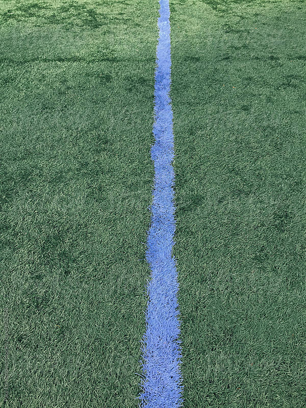Blue boundary line on artificial turf sports field by Paul Edmondson for Stocksy United