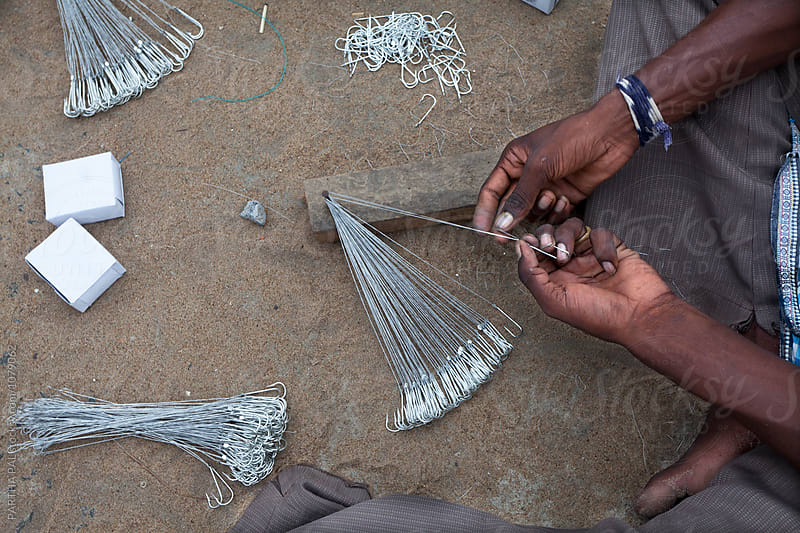 A fisherman fixing fishing hook in the fishing net by PARTHA PAL for Stocksy United