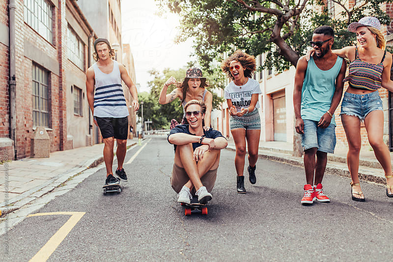 Multiracial young friends having fun on the city street by Jacob Lund for Stocksy United