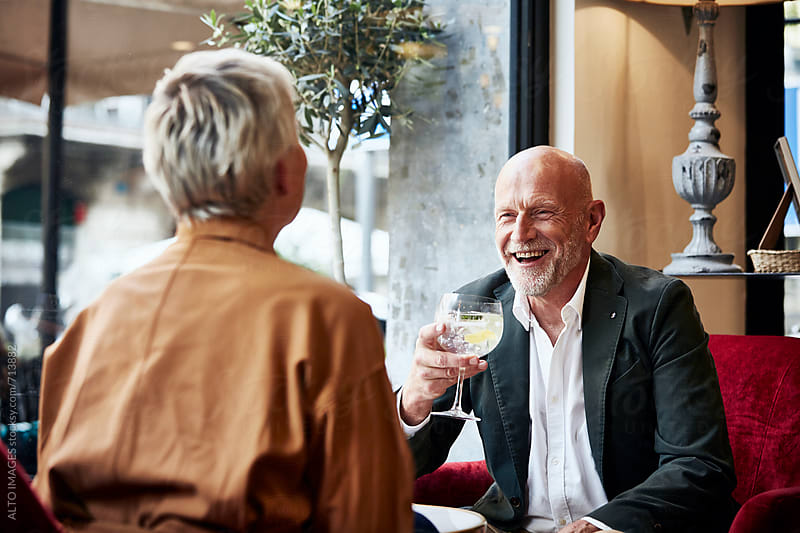 Senior Couple Enjoying Drinks In Restaurant by ALTO IMAGES for Stocksy United