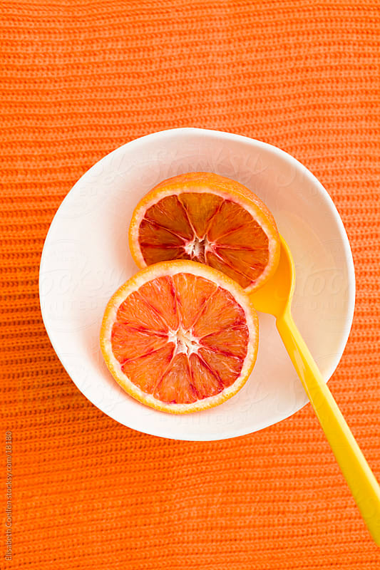 Two halves of a blood orange in a porcelain bowl with a yellow plastic spoon by Elisabeth Coelfen for Stocksy United