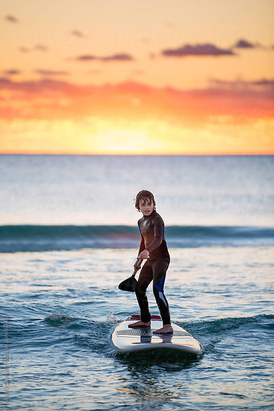 Boy on a stand up paddle board at sunset by Angela Lumsden for Stocksy United
