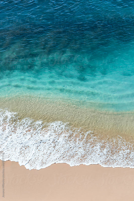 Beautiful turquoise clear sea waves reeaching the sandy shore seen from the air by Jovana Milanko for Stocksy United