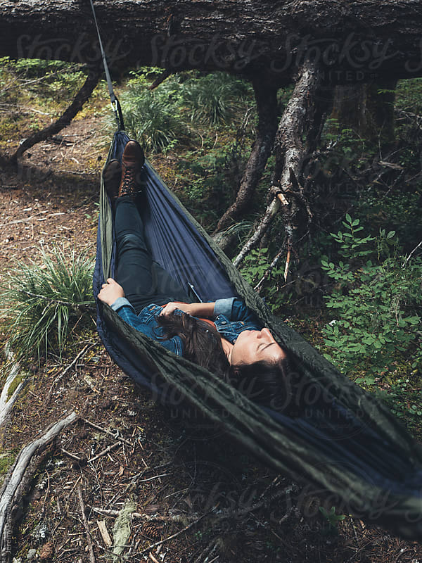 Young hip Asian woman in leather boots sleeping in hammock by Jeremy Pawlowski for Stocksy United