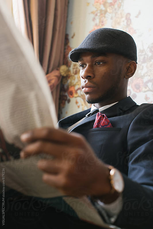 Portrait of Fashionable Young Black Man Reading Newspaper by VISUALSPECTRUM for Stocksy United