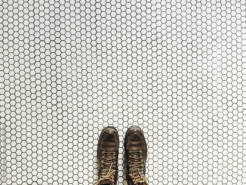 Woman standing on patterned white and black hexagon tile floor by Daring Wanderer for Stocksy United