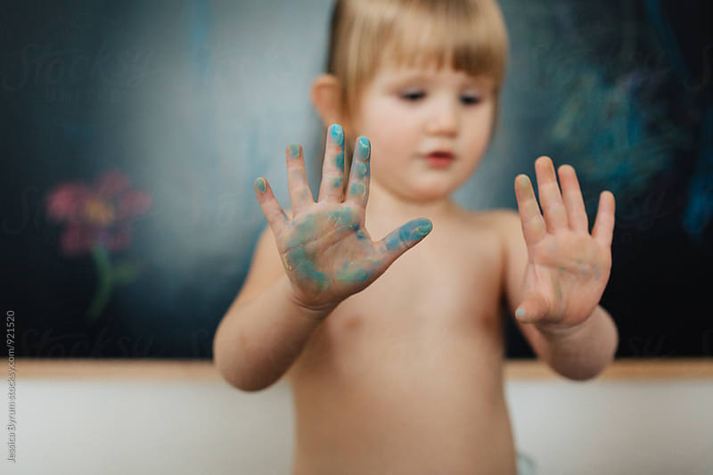 Toddler with chalk on her hand by Jessica Byrum for Stocksy United