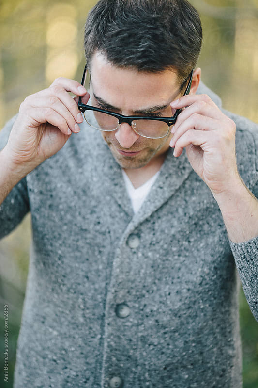 Man adjusting his glasses by Ania Boniecka for Stocksy United