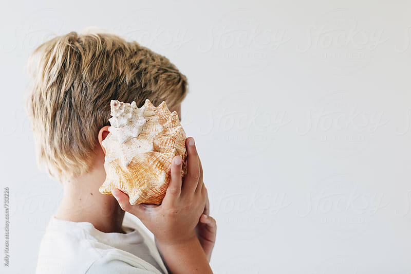 child holding a conch shell to his ear by Kelly Knox for Stocksy United