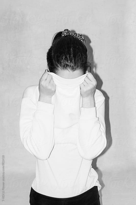Photo of young woman hiding her face with sweater by Danil Nevsky for Stocksy United