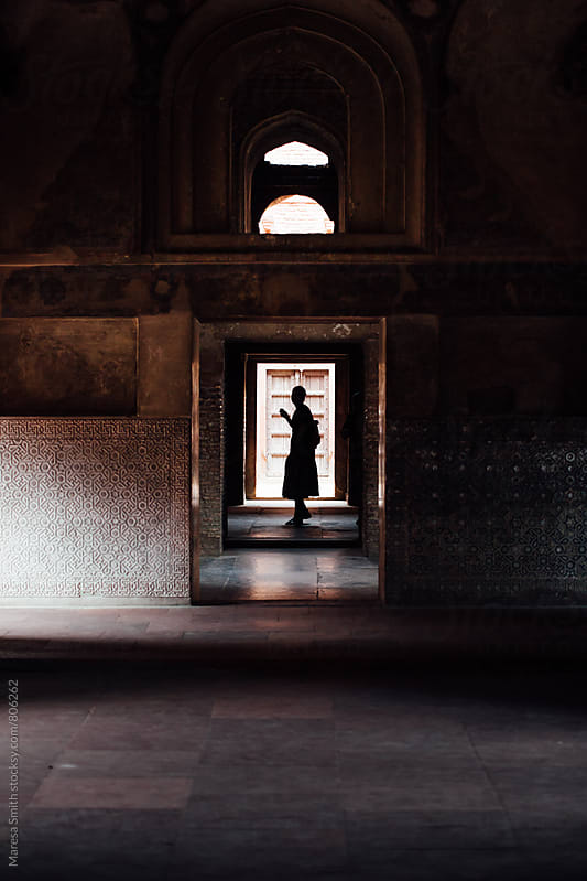 Silhouetted figure in a doorway of an old structure in India by Maresa Smith for Stocksy United