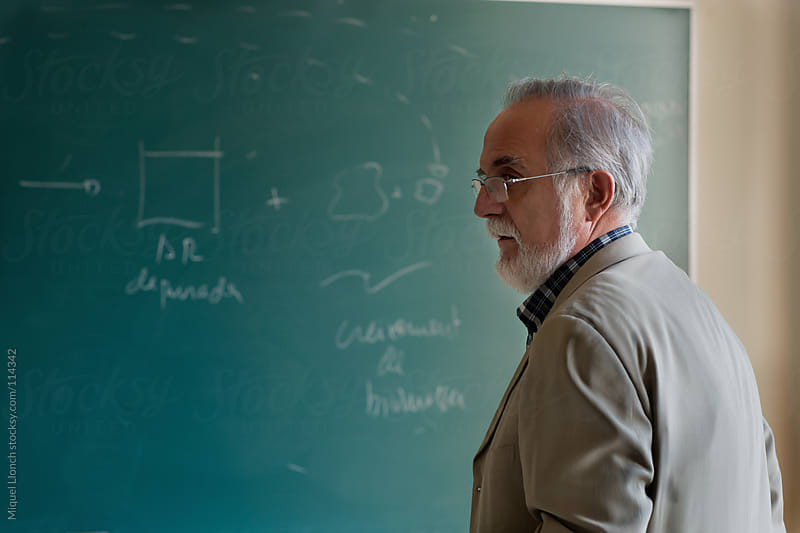 Mature professor in the classroom with green blackboard by Miquel Llonch for Stocksy United