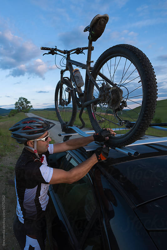 Mountain bike rider fitting his bike in a car rack by RG&B Images for Stocksy United