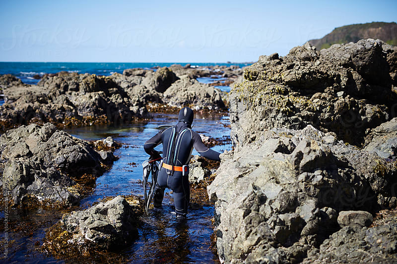 Back view of diver walking through the rocks by Martí Sans for Stocksy United