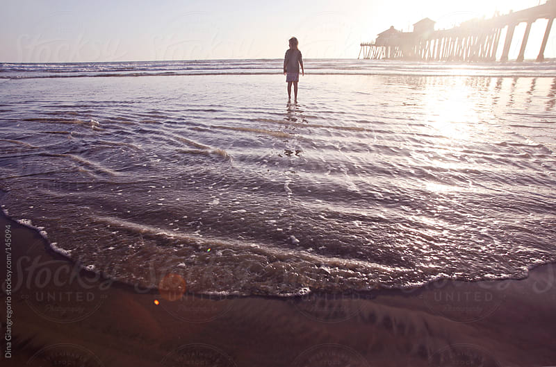 Wide angle back view of child at beach by pier by Dina Giangregorio for Stocksy United