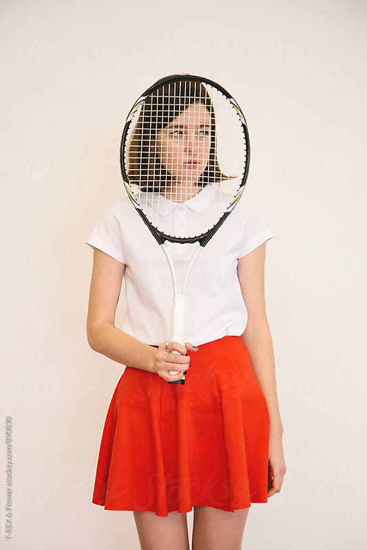 Portrait of girl looking away behind the tennis racket by T-REX & Flower for Stocksy United