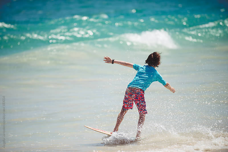 Boy skim boarding onto a low wave at the beach in summer by Angela Lumsden for Stocksy United