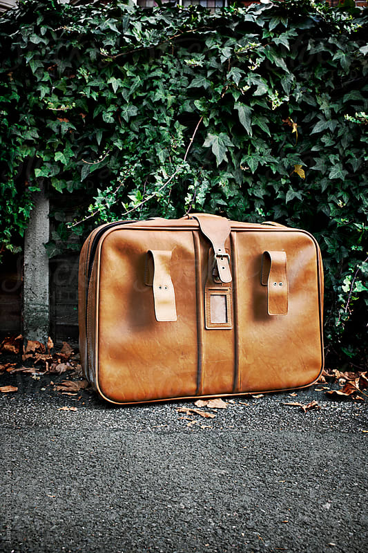 A tan leather suitcase by James Ross for Stocksy United