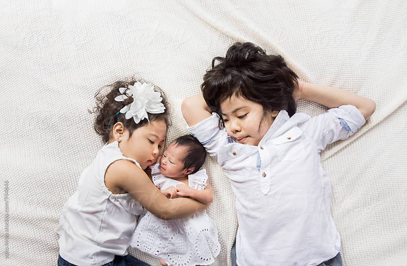 Siblings hugging a newborn baby by yuko hirao for Stocksy United