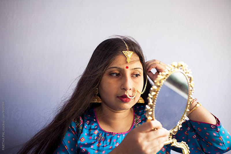 Young Indian woman with traditional dress and Jewelry and looking at the mirror  by PARTHA PAL for Stocksy United