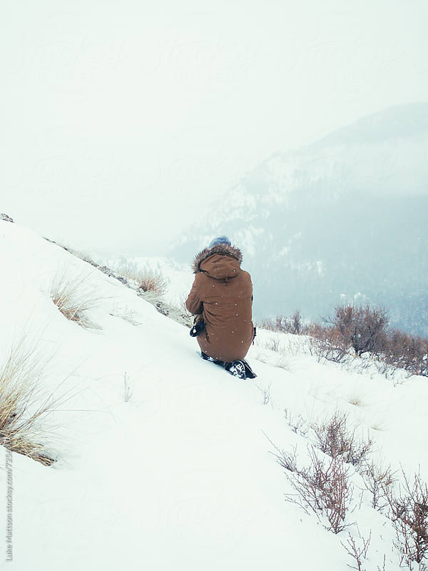 Man Wearing Hooded Winter Coat Crouching In Snow On Hill by Luke Mattson for Stocksy United