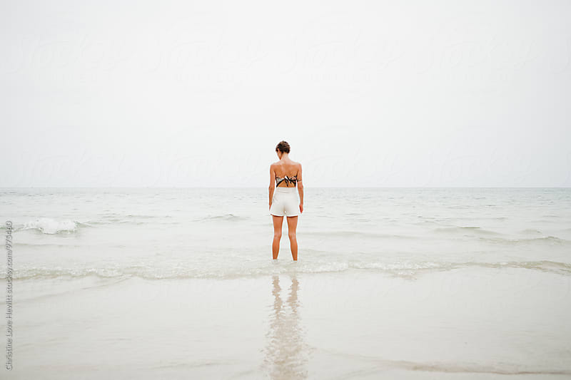Woman standing at the ocean by Christine Hewitt for Stocksy United