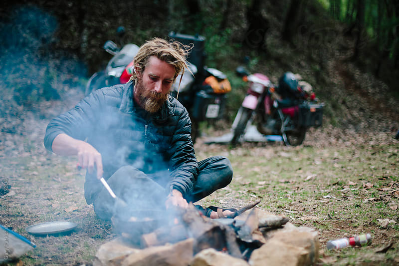 A man cooking over a campfire by Gary Parker for Stocksy United