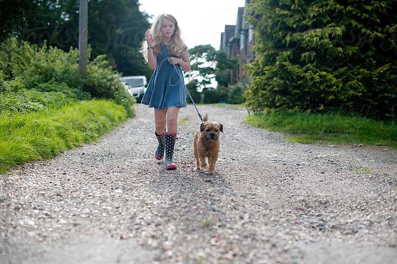 Little girl walking her dog by CHRISTINA K for Stocksy United