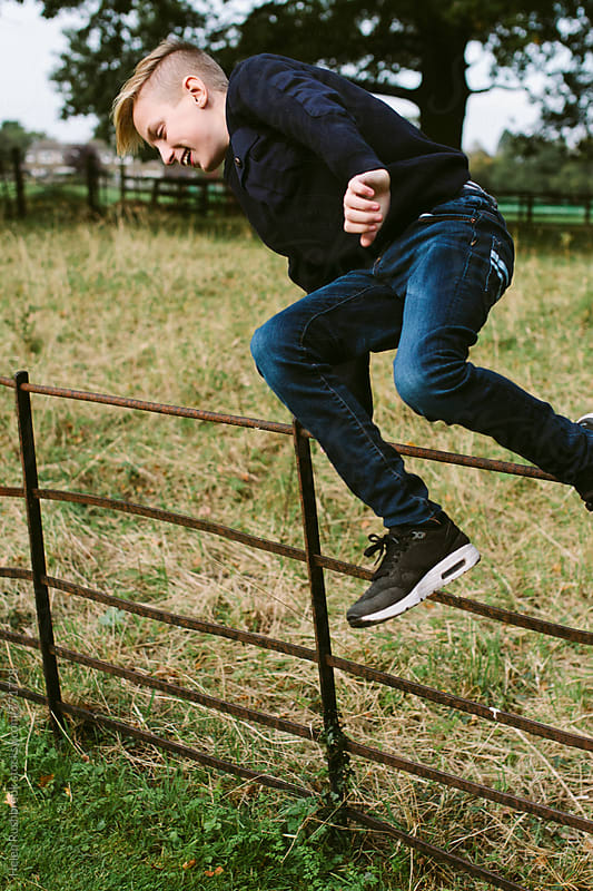 Teenage boy jumping over a fence in the countryside. by Helen Rushbrook for Stocksy United