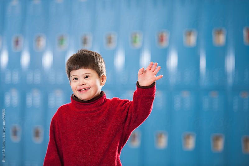 Enthusiastic Elementary School Boy With Down Syndrome Near Lockers by Brian McEntire for Stocksy United