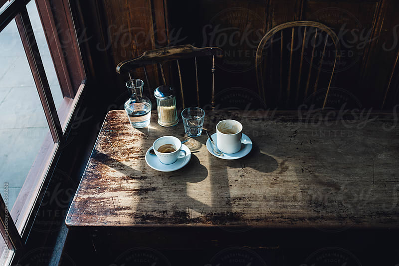 Empty morning coffee cups at worn shabby wood table in a cafeteria by Trent Lanz for Stocksy United