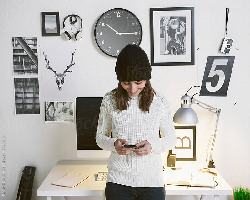 Modern workspace. Creative woman sending a message with smartphone. by BONNINSTUDIO for Stocksy United