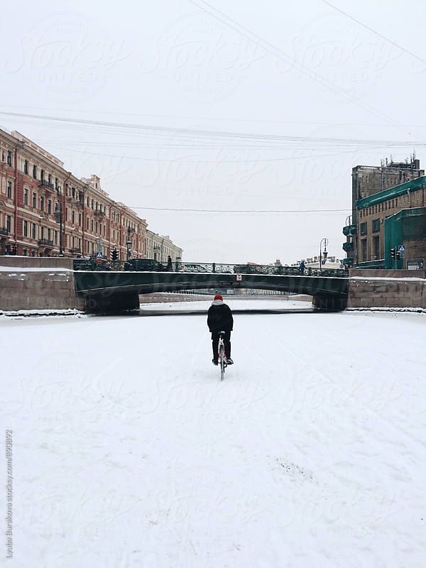 Man riding a bicycle under the bridge by Lyuba Burakova for Stocksy United