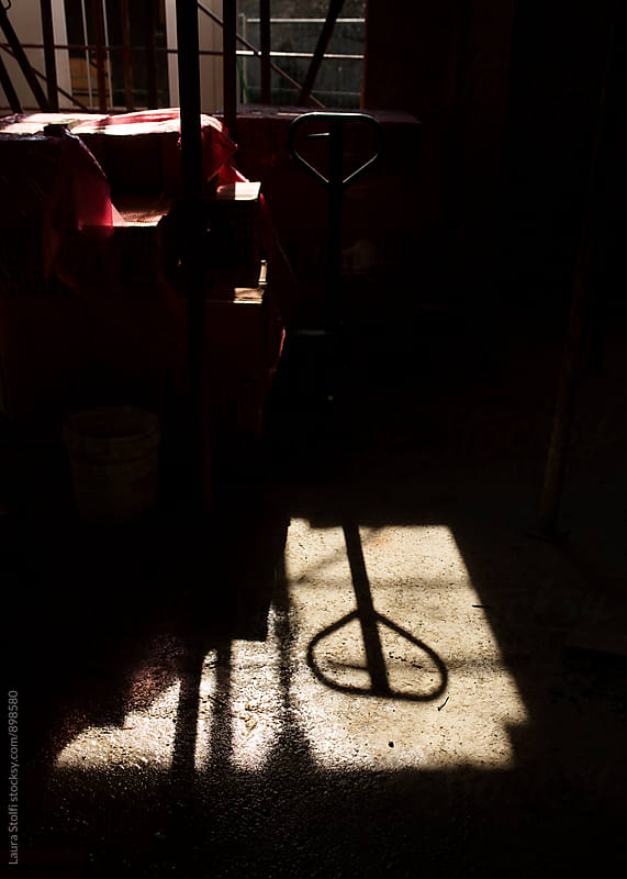 Working cart shadow on the floor at building site by Laura Stolfi for Stocksy United