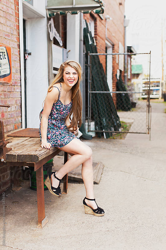 Smiling girl at a back of a warehouse by Ellie Baygulov for Stocksy United