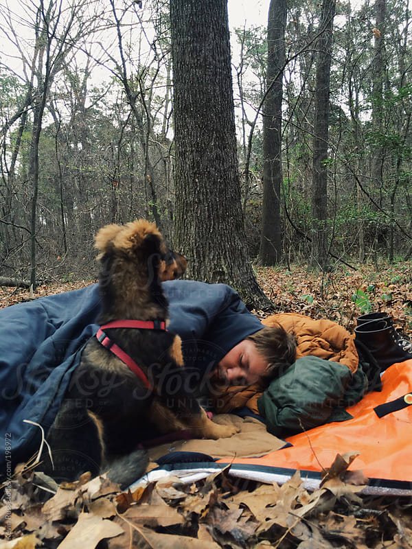 Man Sleeping in the Woods with Puppy on the Lookout by Kevin Russ for Stocksy United