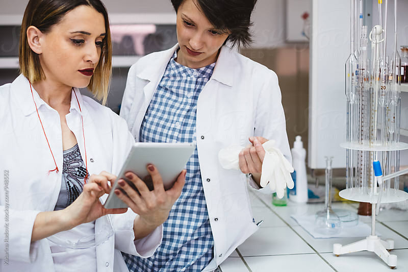 Two Female Chemists Using Tablet While Working by Katarina Radovic for Stocksy United