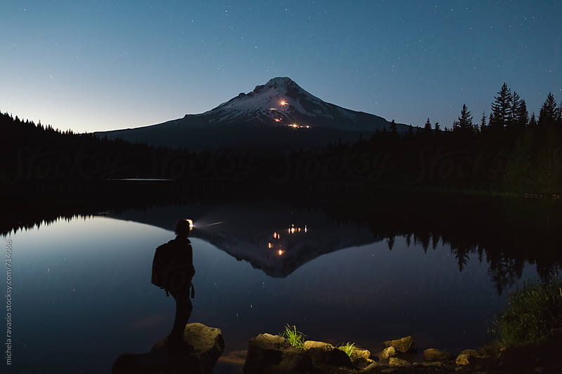 Woman walking along the river of Trillium Lake at night with head torch by michela ravasio for Stocksy United