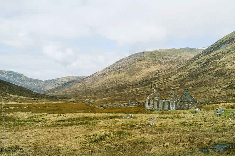 A ruin or abandoned stoned house in a valley in the Scottish Highlands by Ivo de Bruijn for Stocksy United