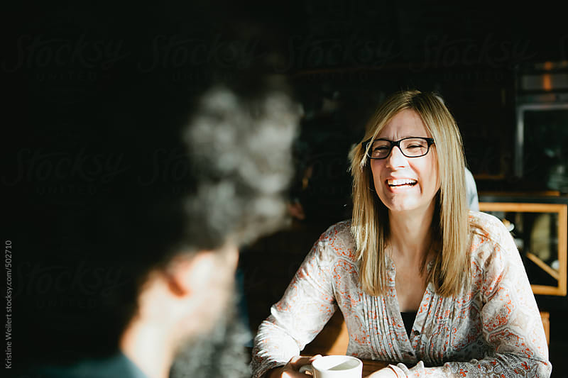 Woman smiling while chatting with a man over coffee by Kristine Weilert for Stocksy United