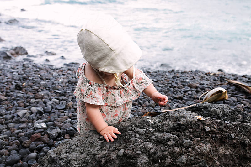Baby playing with rocks on a beach by Treasures & Travels for Stocksy United