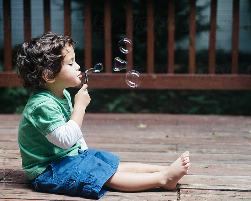 toddler blowing bubbles one of which is almost heart shaped by Tara Romasanta for Stocksy United