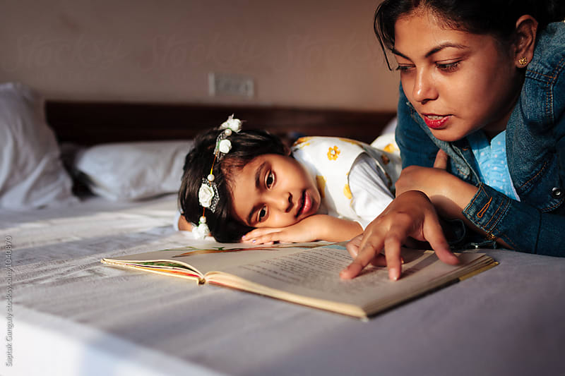 Mother reading a story to her daughter by Saptak Ganguly for Stocksy United