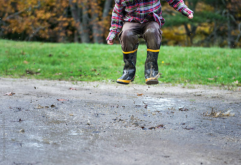 Child is airborne as he jumps into a mud puddle by Cara Dolan for Stocksy United